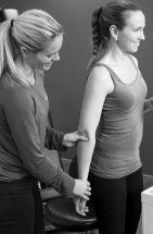 Kiropraktor justere og undersøker albue og skulder på pasient