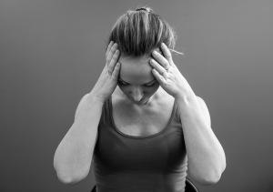Kvinde tar seg til hodet, føler seg svimmel