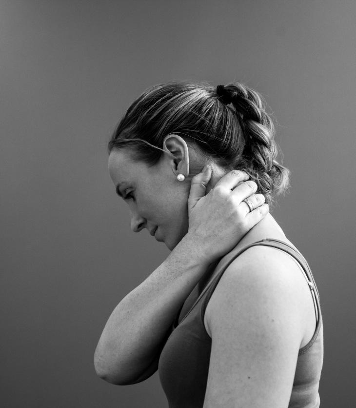 Kvinde som holder seg til nakken fordi hun har vondt i hodet