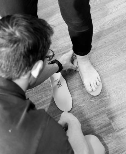 Fysioterapeut undersøker og tilpasser sål til pasient