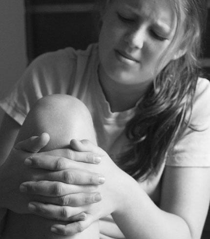 Ung jente med smerter i kneet. Holder seg på kneet med hendene